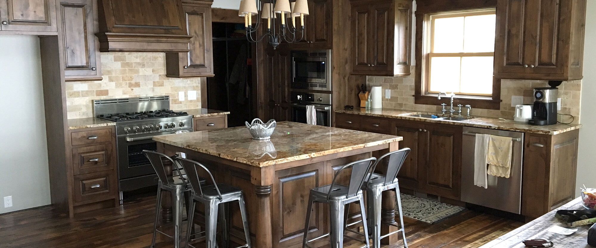 Custom kitchen cabinets made of Alder featuring a square island with corbal legs; designed, built, and installed by finewood Structures of Browerville, MN