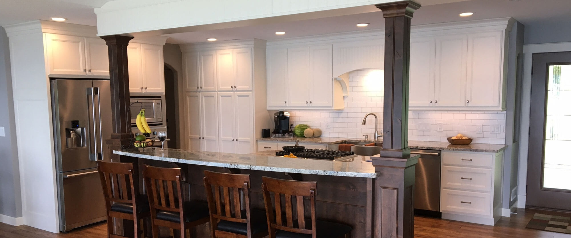 Custom kitchen cabinets made of solid wood and painted white featuring a breakfast bar island; designed, built, and installed by finewood Structures of Browerville, MN