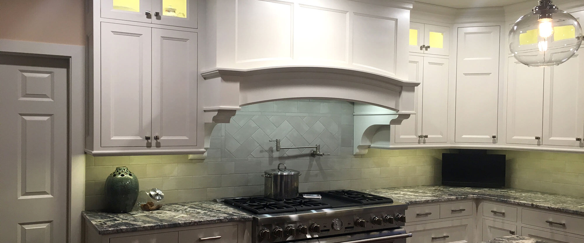 Custom kitchen cabinets made of solid wood and painted white featuring a curved range hood and lighted upper doors; designed, built, and installed by finewood Structures of Browerville, MN