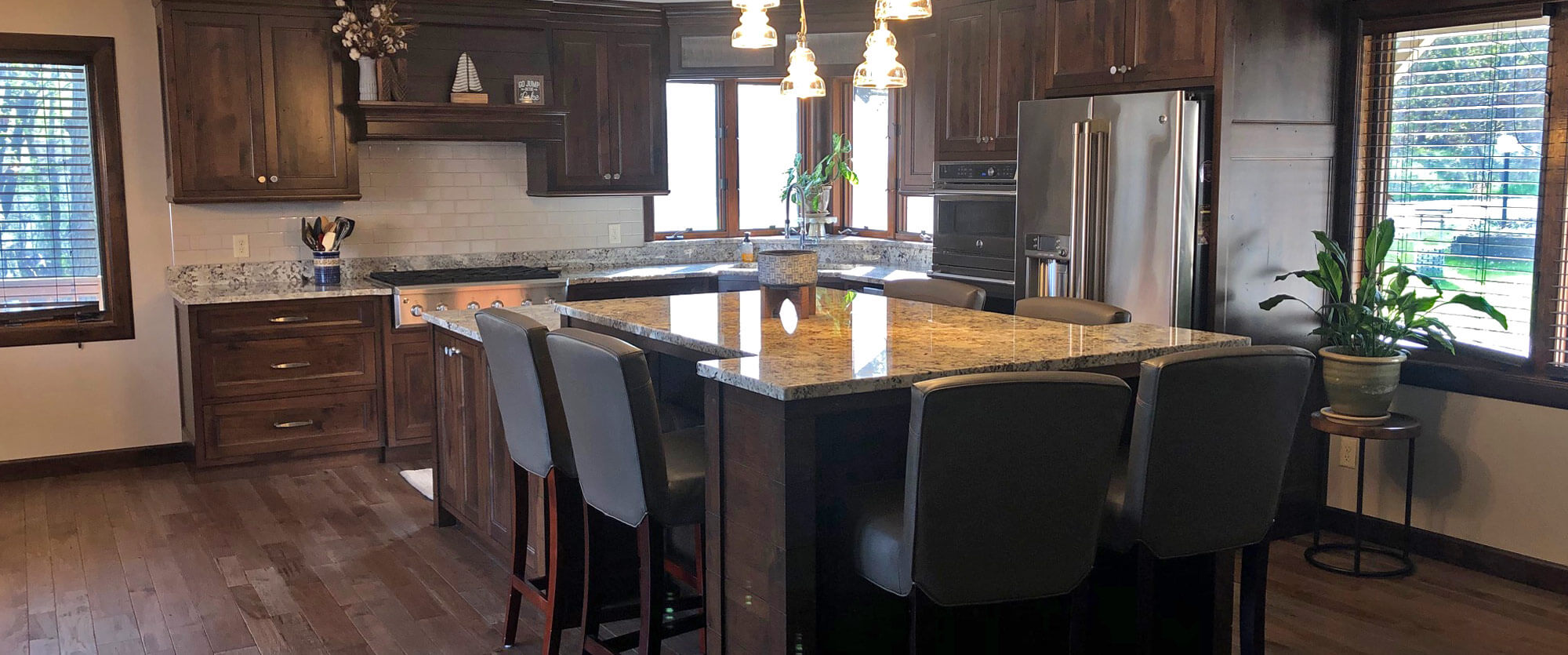 Custom kitchen cabinets made of Alder featuring a corner sink and large center island; designed, built, and installed by finewood Structures of Browerville, MN