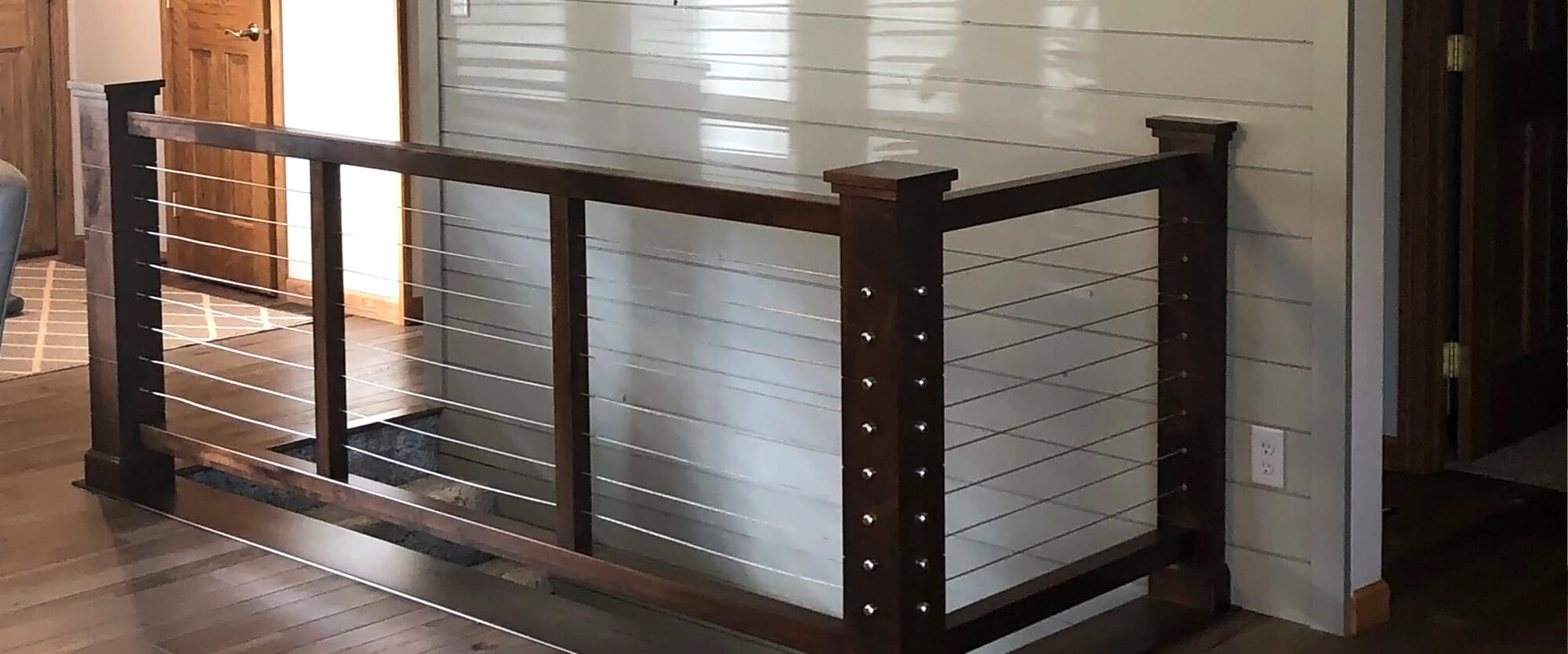 Custom stair hand rail made of solid Alder wood with a ship lap wall behind; designed, built, and installed by finewood Structures of Browerville, MN